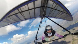Happy smiling woman hang glider pilot high in the sky with cumulus clouds. Selfie by action camera