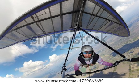 Happy smiling woman hang glider pilot high in the sky with cumulus clouds. Selfie by action camera Сток-фото ©