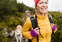 Happy smiling woman hiking in mountains with akita dog, Karkonosze Mountain Range. Young female hiker smiling, sport and trekking in autumn nature.