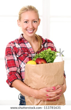 Happy smiling woman holding a grocery bag