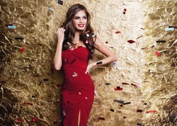 Happy smiling woman in amazing red dress celebrating new year party, posing in gold shine background and  throwing  colorful confetti.