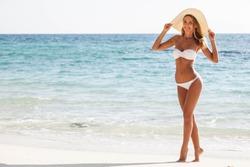 Happy smiling woman in bikini and sunhat on sea beach