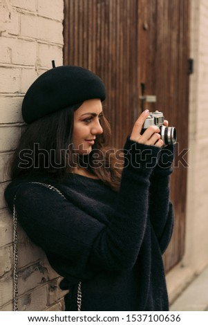happy smiling woman in hat holding retro camera. Photographer making pictures