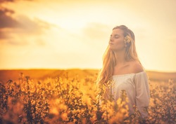 Happy smiling woman in yellow rapeseed field at sunset