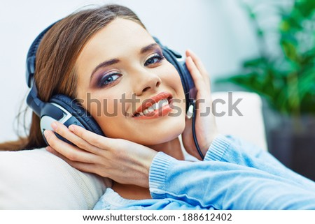 Happy smiling woman listening music with headphones. Smiling girl relax at home.