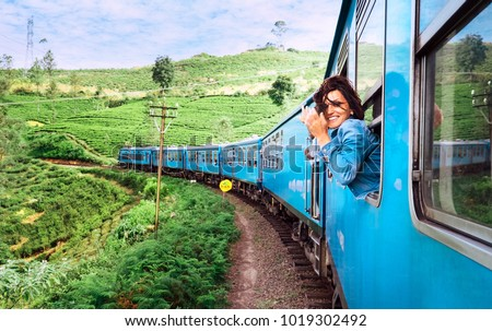Happy smiling woman looks out from window traveling by train on most picturesque train road in Sri Lanka