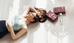 Happy smiling woman lying on floor at home or gym, resting after successful fitness workout. Stretching soft blocks and eco bottle of water. Pleasant fatigue after training. Healthy lifestyle routine