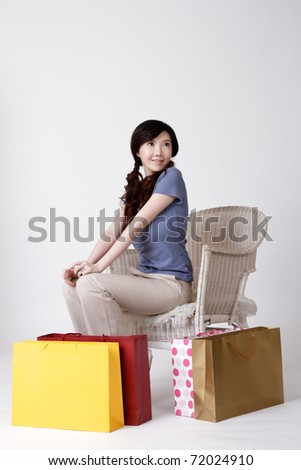Happy smiling woman of shopper put bags on ground and sit on chair.