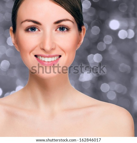 Happy smiling woman over holiday bokeh background with copy-space