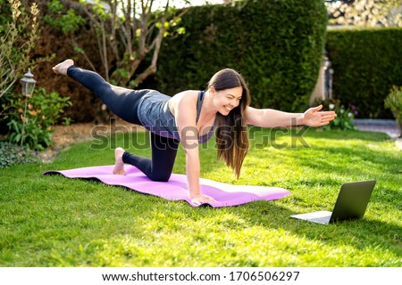 Happy smiling woman practicing pilates lesson online in garden outdoors during quarantine. Doing sport at home following guide or online tutorial or trainer instructions on laptop.