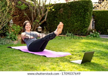 Happy smiling woman practicing pilates lesson online in garden outdoors during quarantine. Doing sport at home following guide or online tutorial or trainer instructions via skype