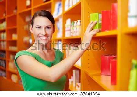 Happy smiling woman shopping for medicine in drugstore