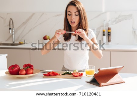 Happy smiling woman taking a picture of vegetable slices on a wooden board with mobile phone while standing at the kitchen