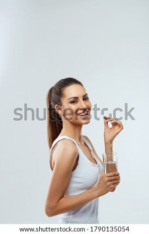 Happy Smiling Woman Taking Pill With Cod Liver Oil Omega-3 And Holding A Glass Of Fresh Water In Morning. Vitamin D, E, A Fish Oil Capsules. Diet. Nutrition. Healthy Eating