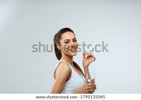 Happy Smiling Woman Taking Vitamin Pils And Holding A Glass Of Fresh Water In Morning. Vitamin D, E, A Fish Oil Capsules,Omega-3. Diet. Nutrition. Healthy Eating