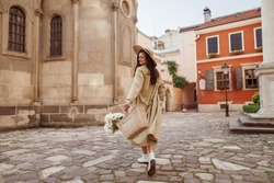 Happy smiling woman wearing straw hat, long trench coat, holding basket with flowers, walking in street of European city. Lifestyle, travel concept. Full-length portrait. Copy, empty space for text