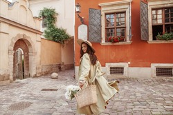 Happy smiling woman wearing straw hat, long trench coat, holding wicker basket with peony flowers, walking in street of European city. Lifestyle, travel concept. F Copy, empty space for text