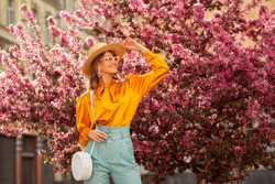 Happy smiling woman wearing trendy straw hat, yellow satin blouse, blue trousers, cat eye sunglasses, with wicker bag, posing in street near pink spring blossom trees. Copy, empty space for text