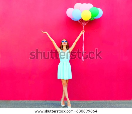 Happy smiling woman with an air colorful balloons over a pink background