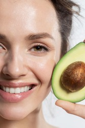 Happy smiling woman with avocado cropped studio portrait. Beautiful vegetarian showing positive emotion on face. Proper nutrition, raw food diet, ketodiet, weight loss. Veganism and vegetarianism