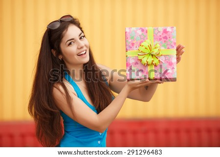 Happy smiling woman with gift box, beautiful girl with birthday gifts outdoor, beautiful female at birthday party with present, joyful lady hold gifts outdoor portrait, instagram style color filter