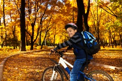 Happy smiling 8 years old black boy with backpack riding a bike in the autumn park full of orange leaves leaning on bicycle stern turning back