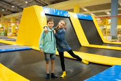 Happy smiling 11 years old kids jumping on trampoline indoors in entertainment center. Active children leisure, jumping and playing on trampoline in sport center. Amusement park. Sport activity.