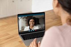 Happy smiling young african female blogger in sportswear talk to web cam broadcast live from home on personal channel. Young black woman glad to answer friend by video call on pc screen in messenger