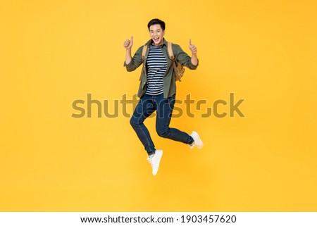 Happy smiling young Asian tourist man with backpack jumping and giving thumbs up isolated on yellow background