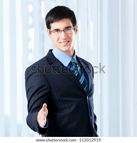 Happy smiling young business man giving hand for handshake, at office