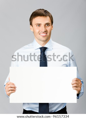 Happy smiling young business man showing blank signboard, over gray background