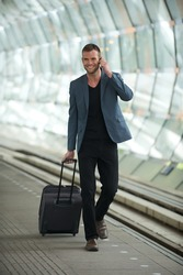 Happy smiling young business man wearing casual suit and walking in the train station with a phone and suitcase in hand