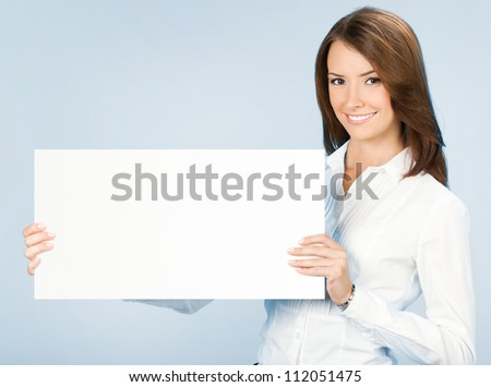 Happy smiling young business woman showing blank signboard, over blue background
