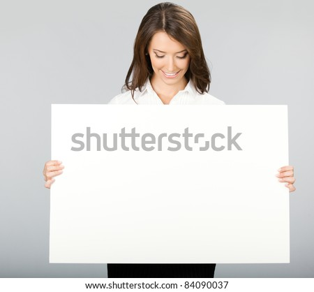 Happy smiling young business woman showing blank signboard, over grey background