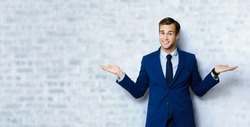 Happy smiling young businessman in blue confident suit, showing something or empty copyspace area for slogan, advertising or text, standing over loft style wall background.