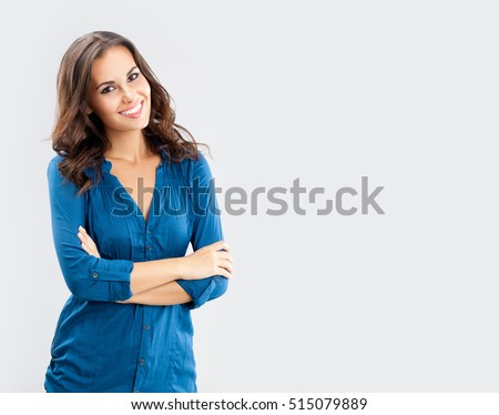 Happy smiling young businesswoman, on grey background. Caucasian brunette model in business concept studio shoot. Blank copyspace area for advertise text or slogan. #515079889