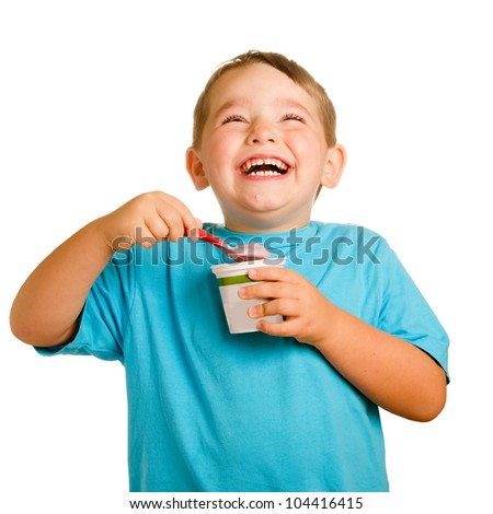 Happy smiling young child eating yogurt isolated on white