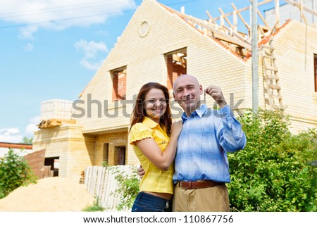 Happy smiling young couple showing a pair of keys of their new house