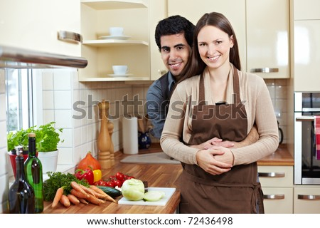 Happy smiling young couple standing in a kitchen