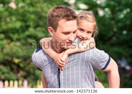 Happy smiling young father and daughter playing in the park