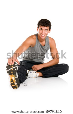 Happy smiling young fitness man sitting and making stretching exercises after gym isolated on white background