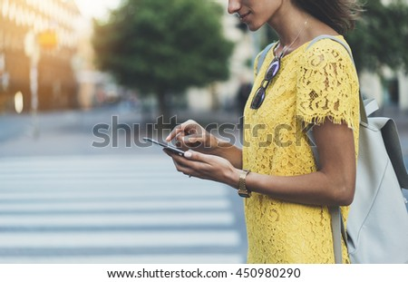 Happy smiling young girl using modern smart phone while standing at crosswalk, hipster girl writing text message on internet via cellphone, attractive woman wearing yellow dress, walking in the city