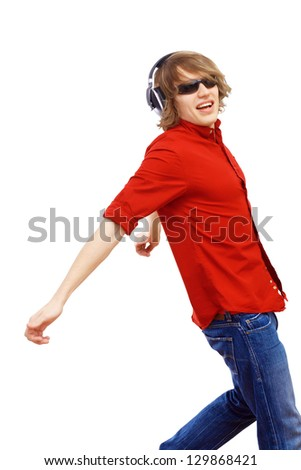 Happy smiling young man dancing and listening to music