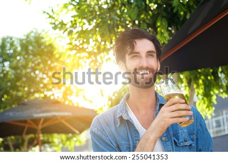 Happy smiling young man drinking beer at outdoor bar in summer