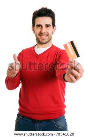 Happy smiling young man holding a credit card and gives thumb up, isolated on white background