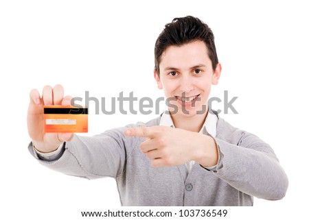 Happy smiling young man holding a credit card and pointing isolated on white background