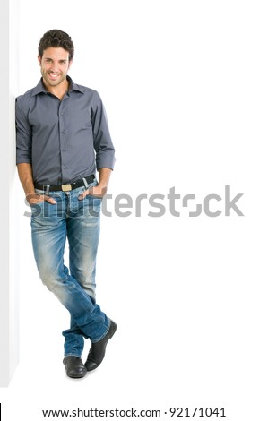 Happy smiling young man leaning against white wall with copy space an the right - stock photo