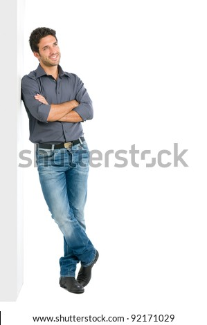 Happy smiling young man leaning against white wall with dreaming and pensive expression, copy space on the right