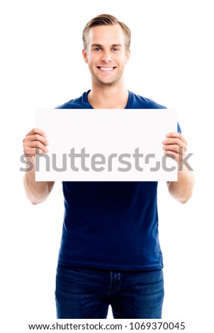Happy smiling young man showing blank signboard with empty copyspace area for slogan or advertising text message, isolated on white background. Caucasian male model in advertisiment concept. #1069370045
