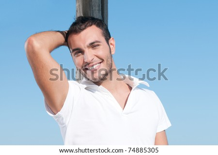 Happy smiling young man taking a break outdoor in summer